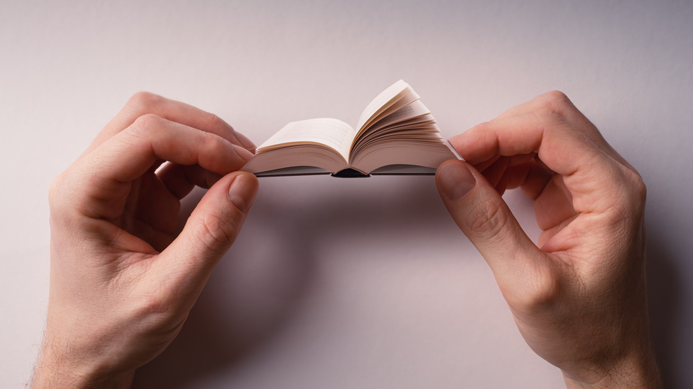Two Hands Holding Open Tiny Paper Book on Light Background