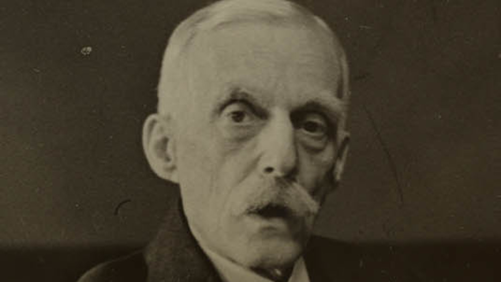 Andrew Mellon seated at desk