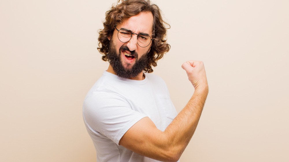 Guy with a beard flexing his biceps