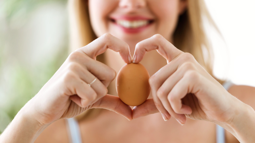 Woman holding brown egg