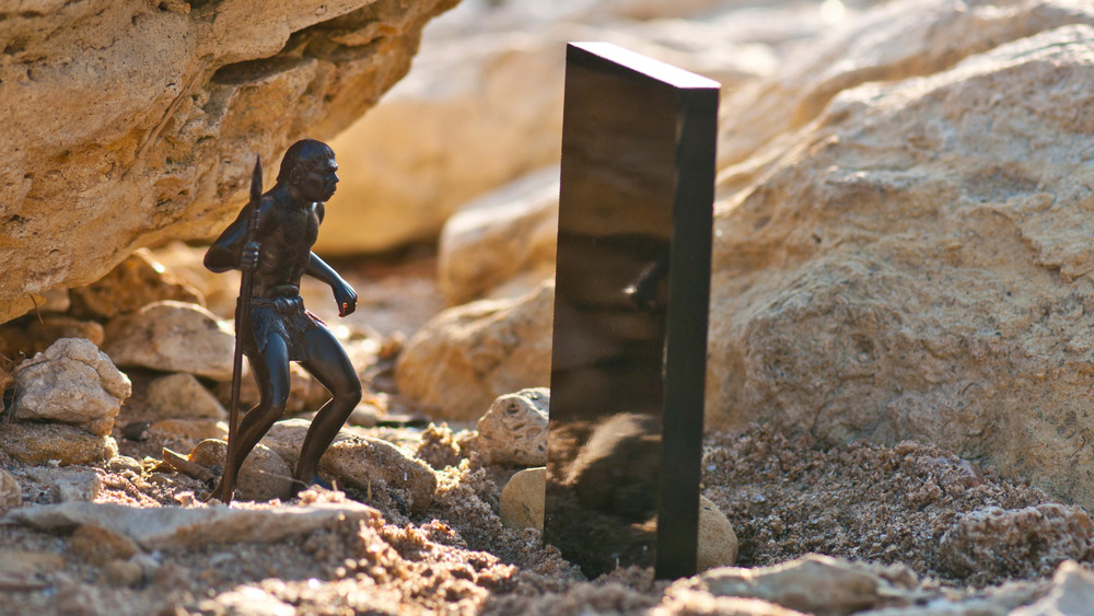 Black monolith on old sandstone rock near the sea coast and Cro-Magnon man with a spear