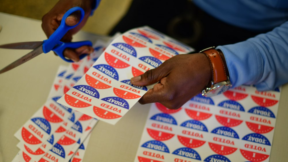 """A volunteer cuts out """" I VOTED TODAY"""" stickers for voters queueing outside of a satellite polling station on October 27, 2020"""