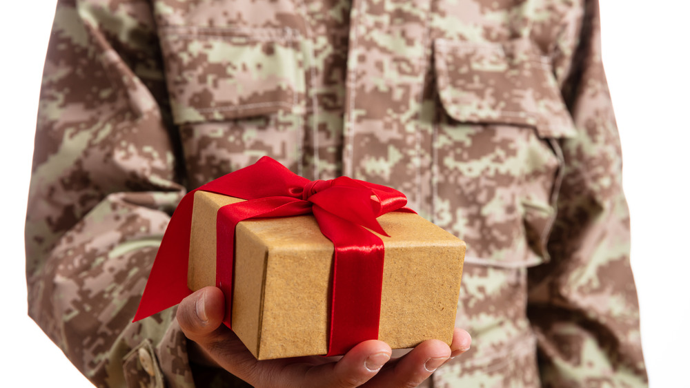 Army soldier holding a Christmas gift