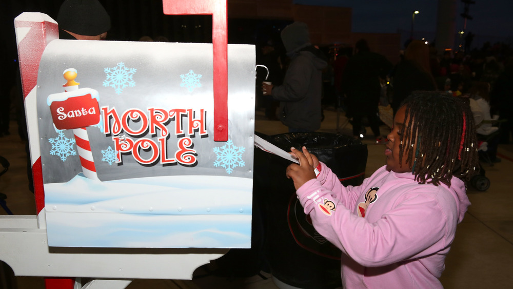 A girl drops a letter to Santa in the special North Pole mailbox before the Christmas tree lighting and grant ceremony at Texas Motor Speedway